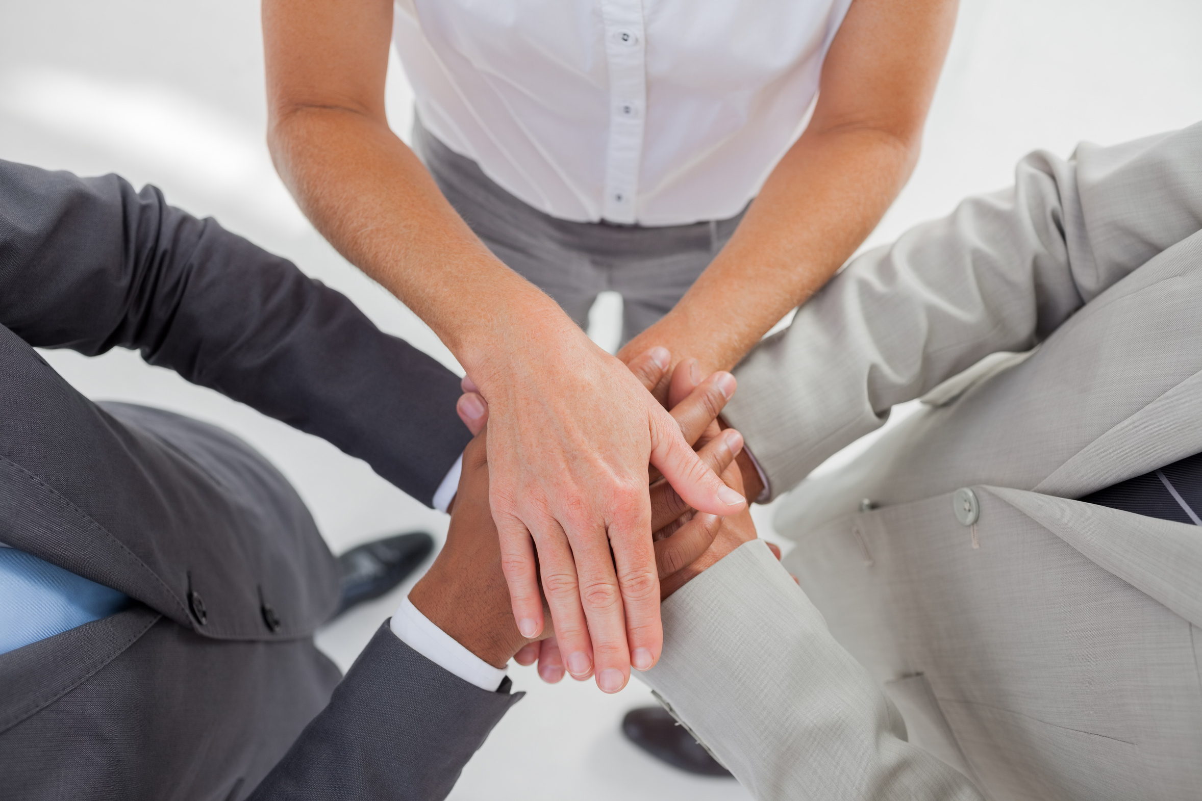 United team piling up their hands together in the workplace